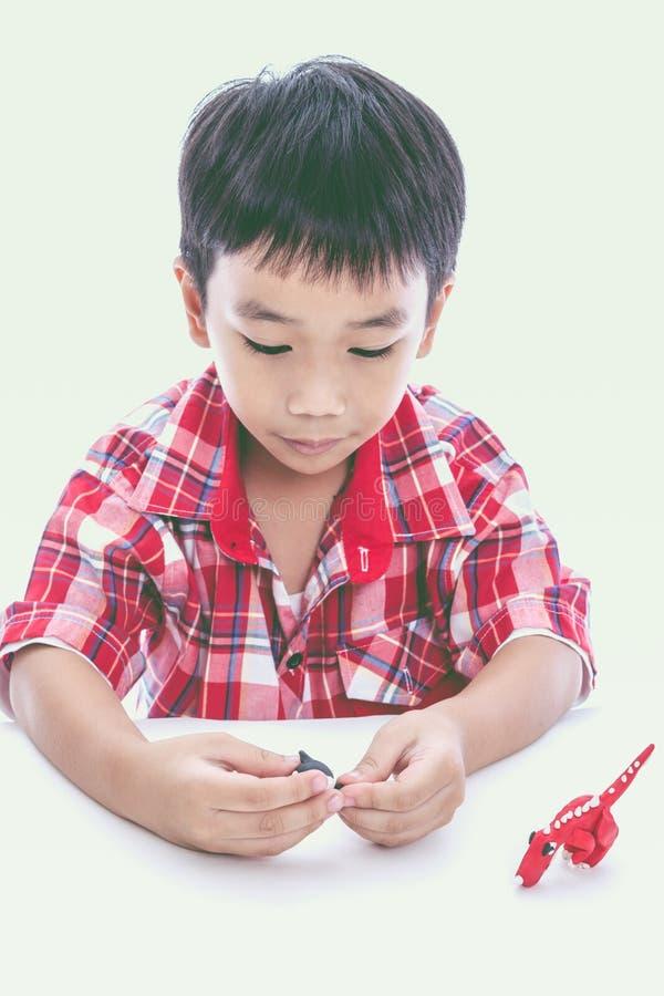 Ребенок отливая его в форму работает от глины, на белизне Усильте imag стоковые изображения rf