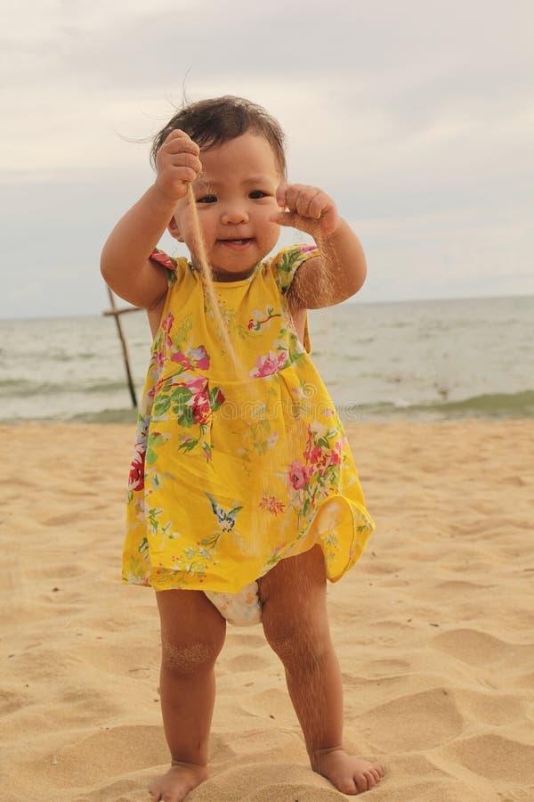 Ребенок очень счастлив когда она играет песок на пляже в летнем дне стоковые изображения rf