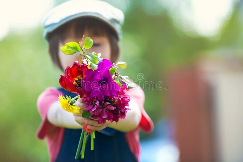 Ребенок дошкольного возраста, держа букет полевых цветков, собрал для m стоковое изображение rf