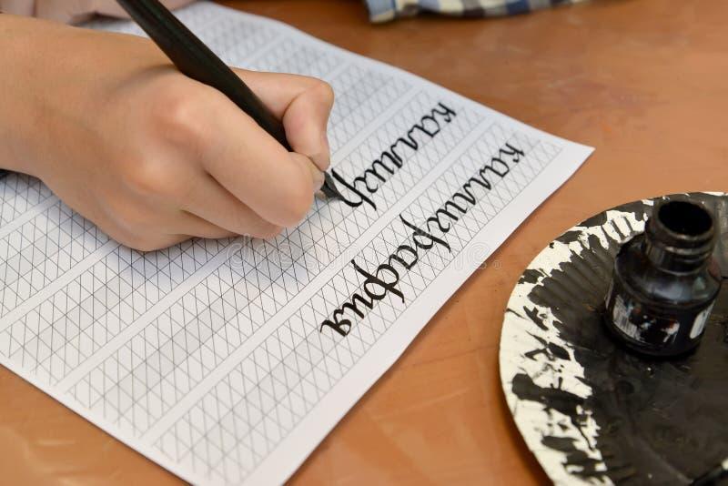 """Ребенок пишет слово """"каллиграфию """"с авторучкой Русский текст - каллиграфия стоковая фотография rf"""