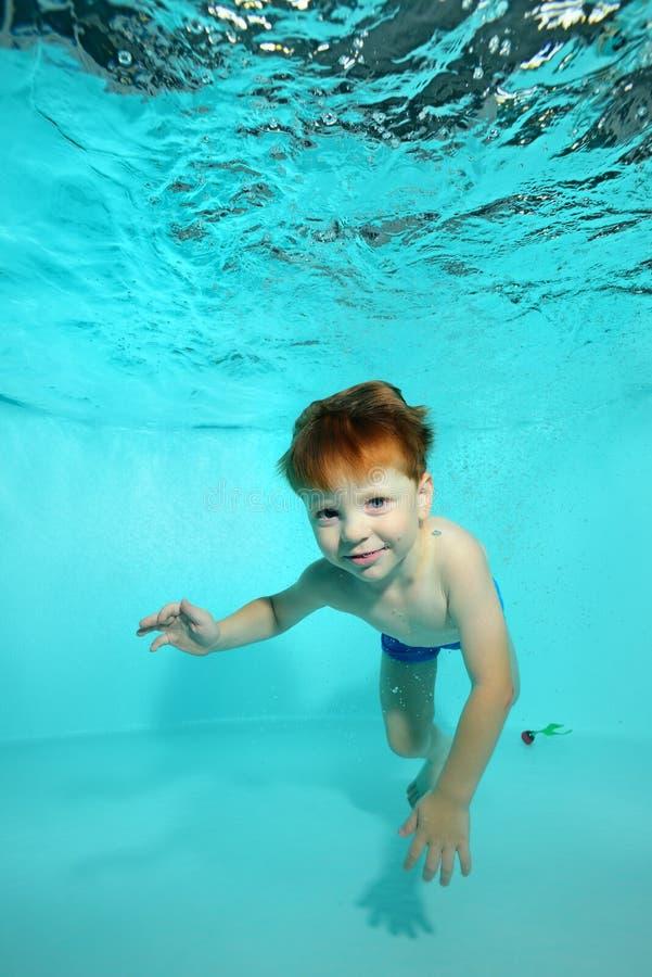 Ребенок плавает под водой в бассейне на голубой предпосылке, смотрит камеру и улыбки стоковые изображения