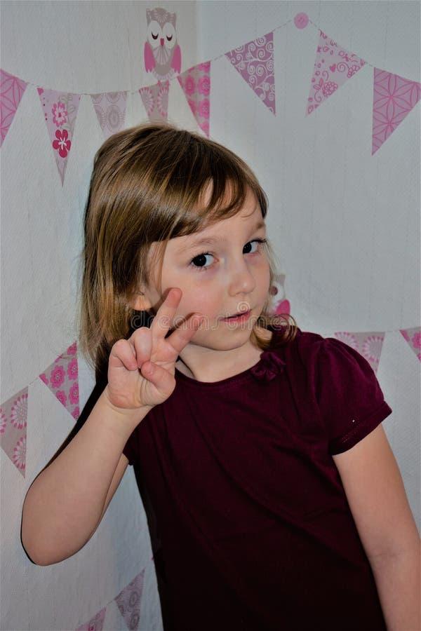 Ребенок показывает символ победы с его пальцами Немного 5 лет старой девушки стоковая фотография