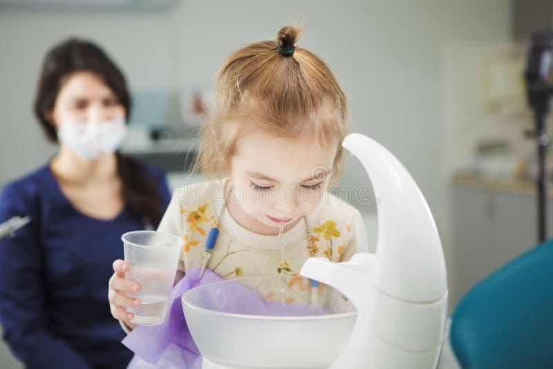 Ребенок полощет вне рот и вертел в специальной раковине стоковое изображение rf