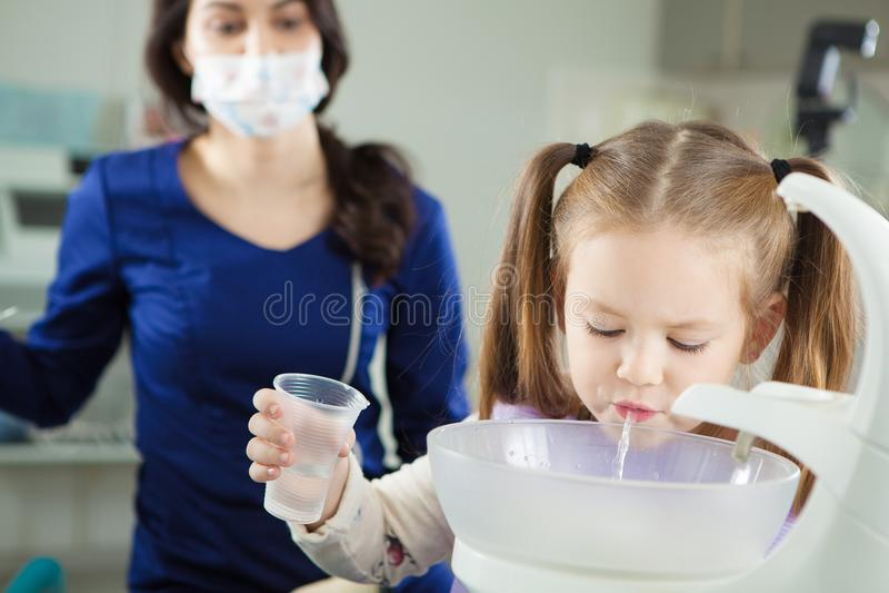 Ребенок полощет вне рот и вертел в специальной раковине стоковые изображения