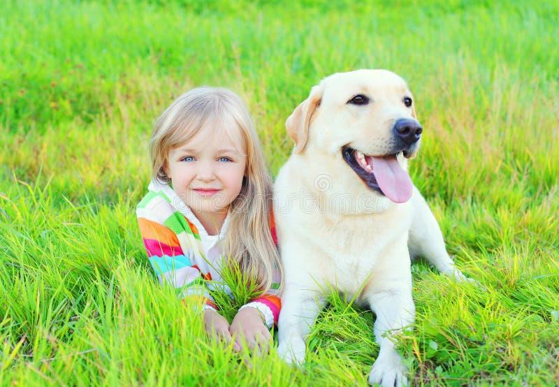 Ребенок портрета и retriever labrador выслеживают лежать на траве стоковая фотография rf