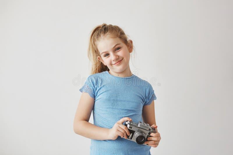 Ребенок портрета o симпатичный белокурый в голубой усмехаться футболки, стоя с камерой фото в руках представляя для альбома школы стоковые изображения