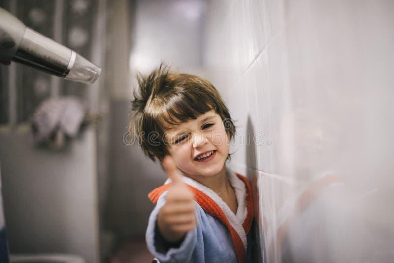 Ребенок после того как ванна приходит он сушит его волосы стоковое изображение rf