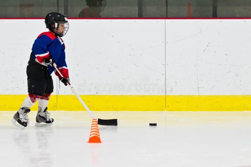 Ребенок практикует stickhandling на практике хоккея на льде стоковые изображения