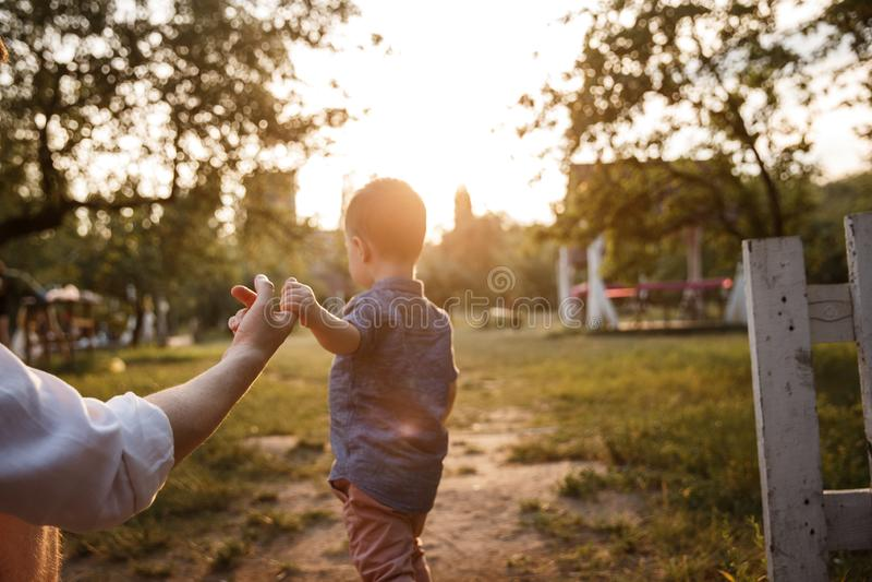 Ребенок принимает его отца пальцем и идет вперед Вечер приходит стоковое фото