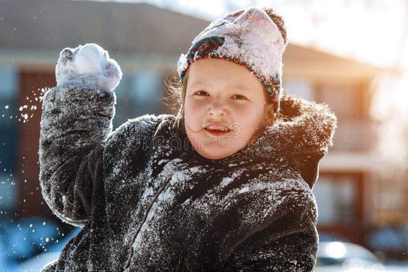 Ребенок при лопаткоулавливатель играя вне двери в сезоне зимы Счастливая маленькая девочка играя в снежном ландшафте стоковые фото