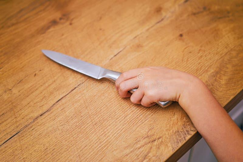Ребенок пробует получить кухонный нож стоковое фото rf