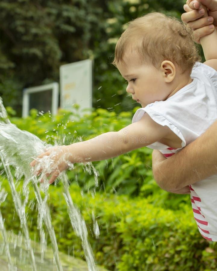 Ребенок протягивает ее руку к фонтану, младенец играет с двигателями воды в парке Ребенок на прогулке в играх парка стоковые изображения rf