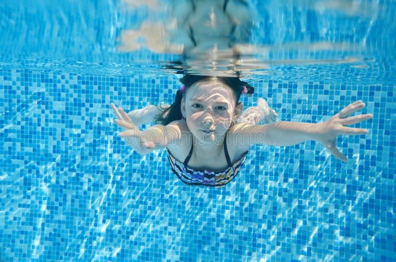 Ребенок плавает в бассейне подводном, счастливая активная девушка ныряет и имеет потеху под водой, фитнесом ребенк и спортом стоковая фотография rf