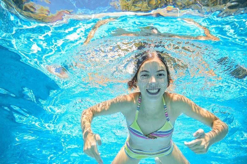 Ребенок плавает в бассейне под водой, девушка имеет потеху в воде стоковое изображение rf