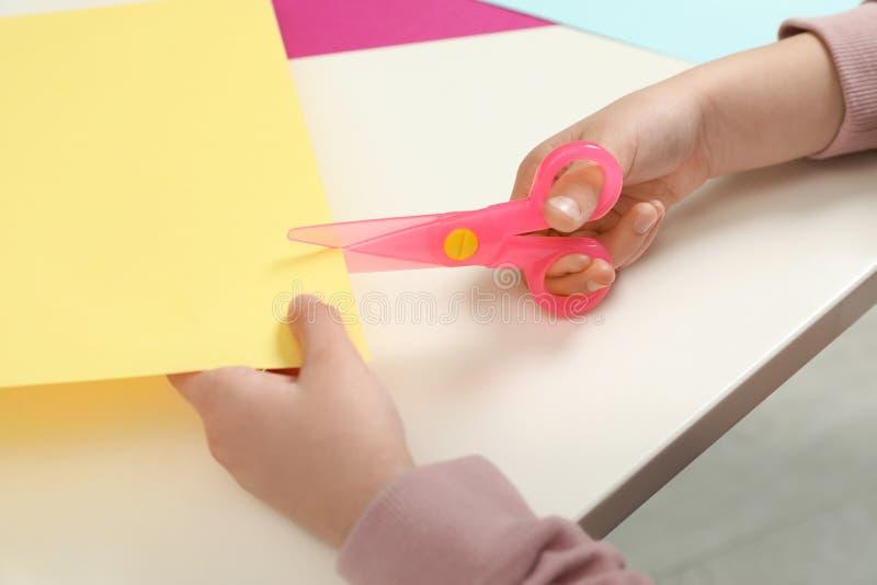 Ребенок режа бумагу цвета с пластиковыми ножницами на таблице стоковая фотография