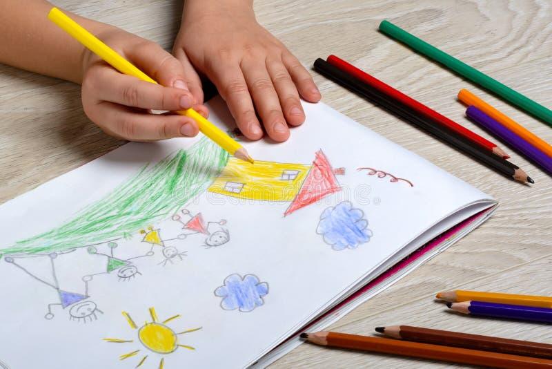 Ребенок рисует его семью на куске бумаги с покрашенными карандашами Моя счастливая семья Концепция психологии ребенка стоковые изображения