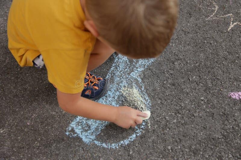 Ребенок рисует покрашенные изображения на улице мела, асфальте стоковые фотографии rf