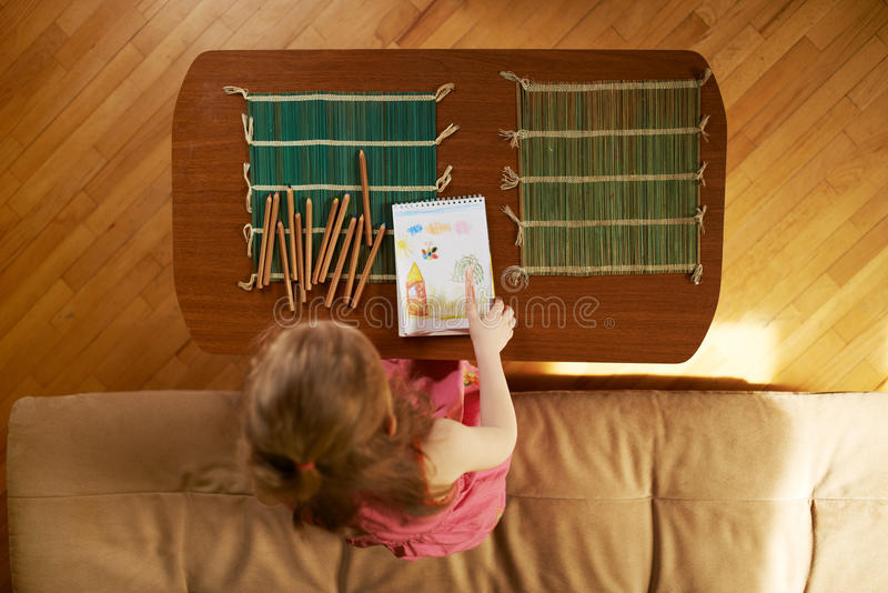 Ребенок рисует с карандашами на таблице стоковое фото rf