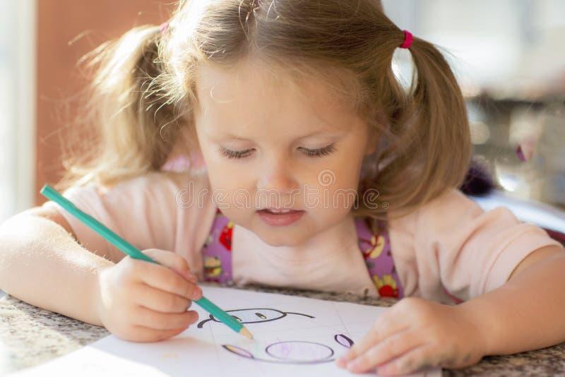 Ребенок рисует с карандашем и улыбками стоковая фотография