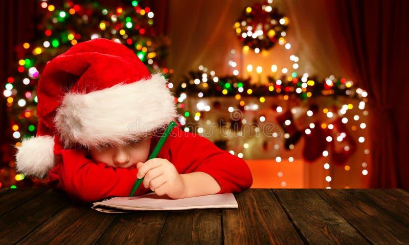 Ребенок рождества пишет письмо Санта Клауса, ребенк в сочинительстве шляпы стоковые изображения rf