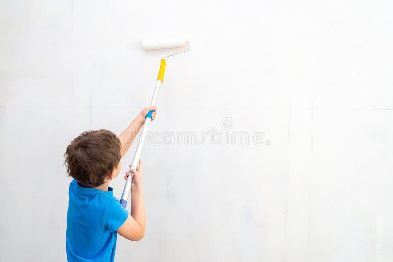 Ребенок свертывает ролик в краске на стене заканчивая работа в предпосылках художника красит стены Ремонт предпосылок стоковая фотография