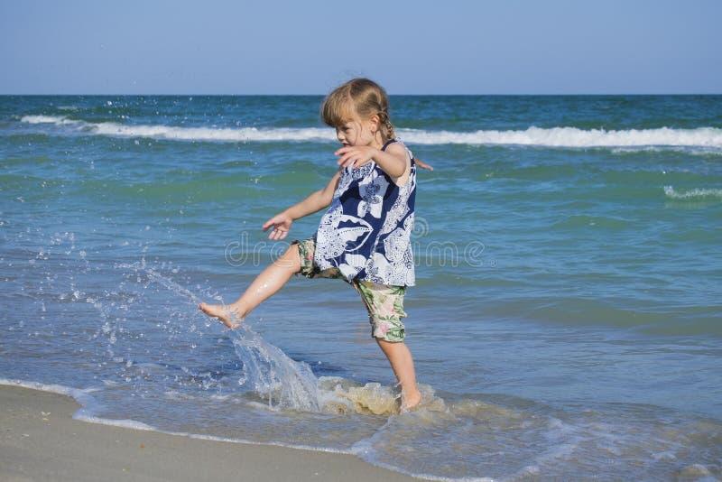 Ребенок свирепствуя на пляже моря ломая воду - вниз стоковые изображения rf