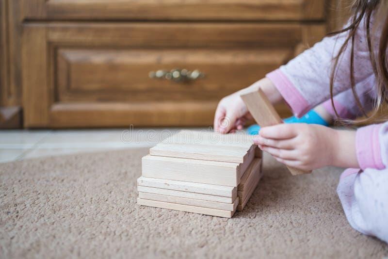 Ребенок сидит на ковре и игре деревянными игрушками, развитии, крупном плане стоковая фотография rf