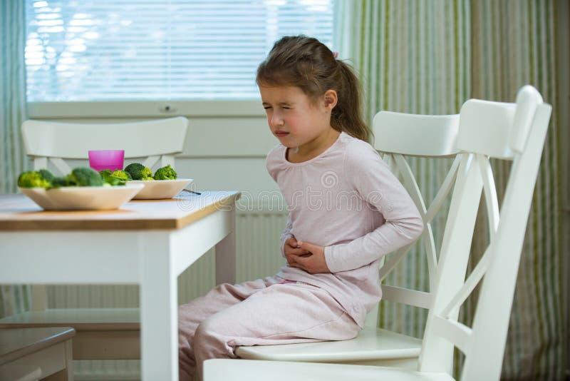 Ребенок сидя на таблице в кухне с болью в животе стоковое фото