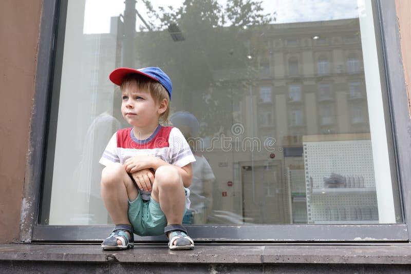 Ребенок сидя на windowsill стоковые изображения rf