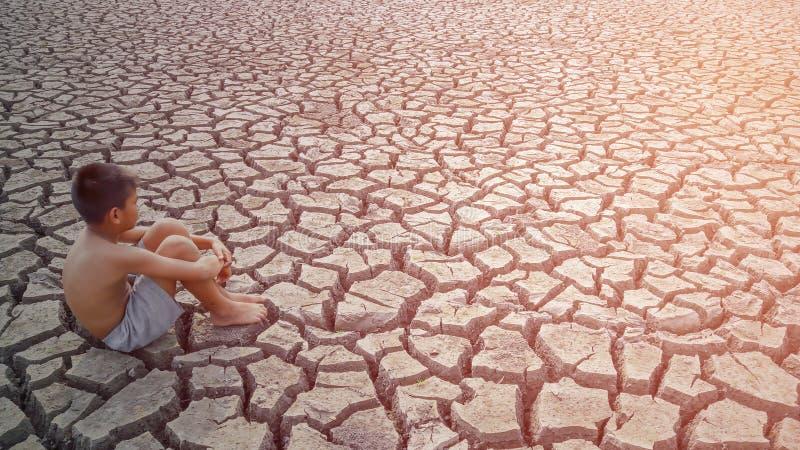 Ребенок сидит на треснутой земле стоковое изображение rf