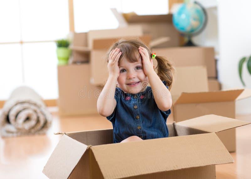Ребенок смотря из коробки в новой комнате после двигать стоковая фотография rf