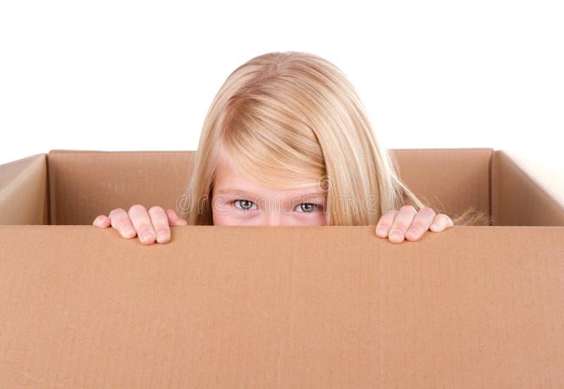 Ребенок смотря из коробки стоковое изображение