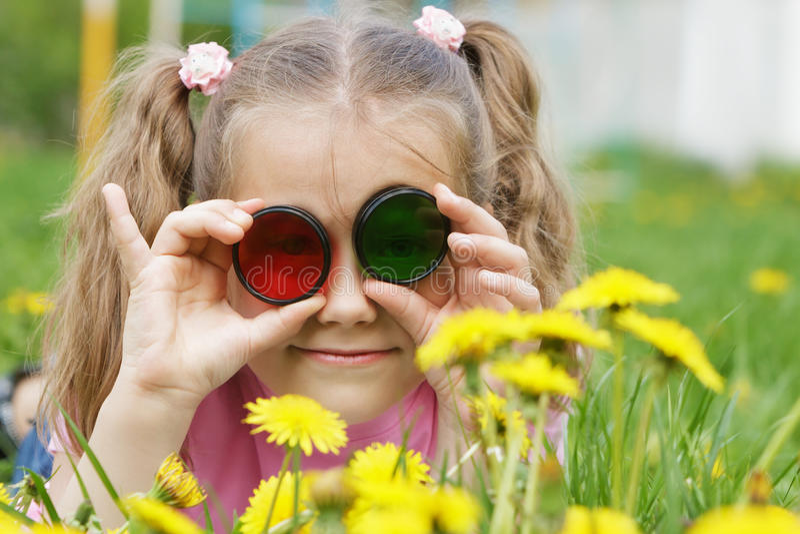 Ребенок смотря через покрашенное стекло (фильтры фото) на dandeli стоковое фото rf