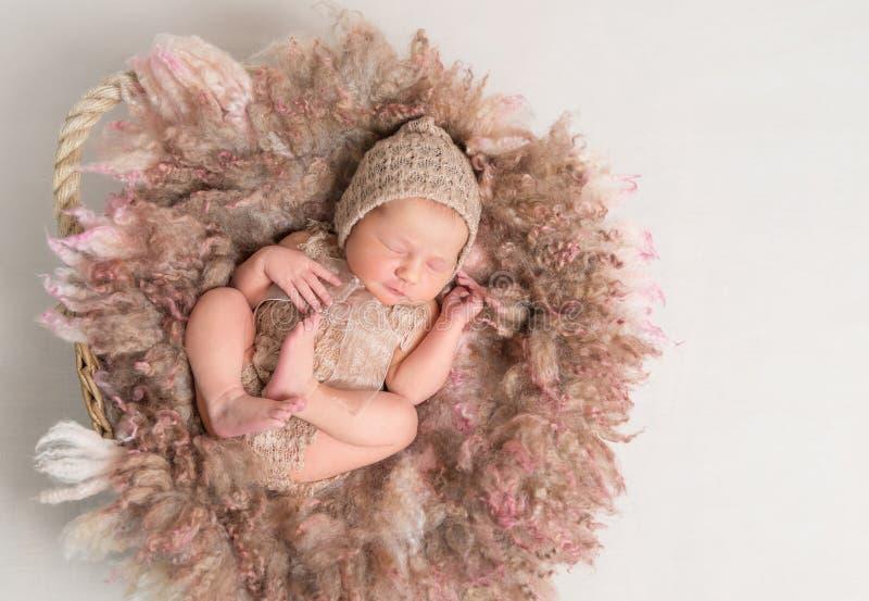 Ребенок спать на меховой подушке, в связанном костюме стоковые фото