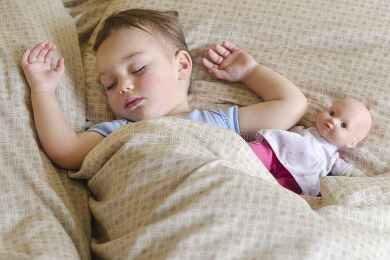Ребенок спать с куклой стоковое фото rf