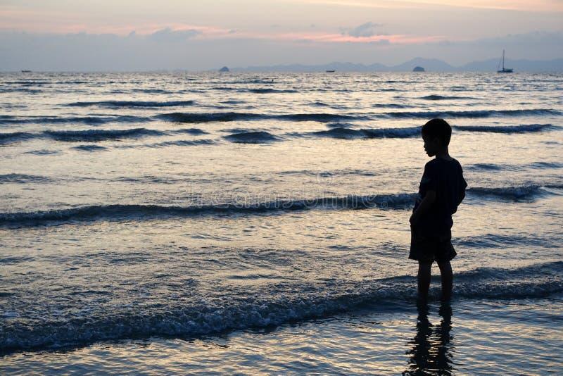 Ребенок стоит в море захода солнца в Krabi, Таиланде стоковые изображения