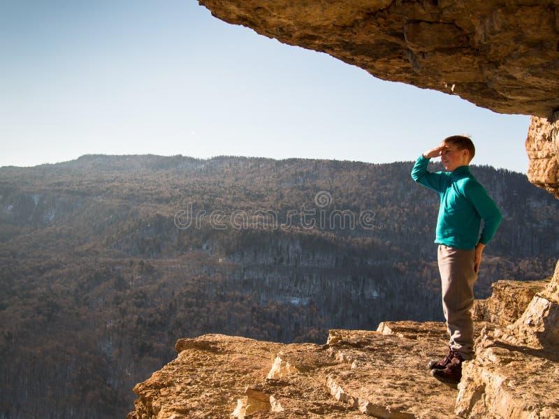 Ребенок стоя на верхней части горы стоковые фото
