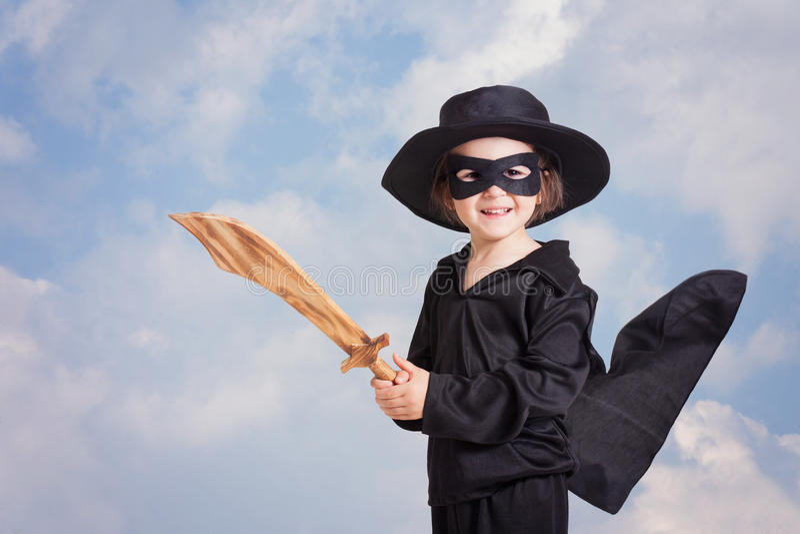 Ребенок супергероя с sward и костюм на предпосылке голубого неба стоковая фотография rf