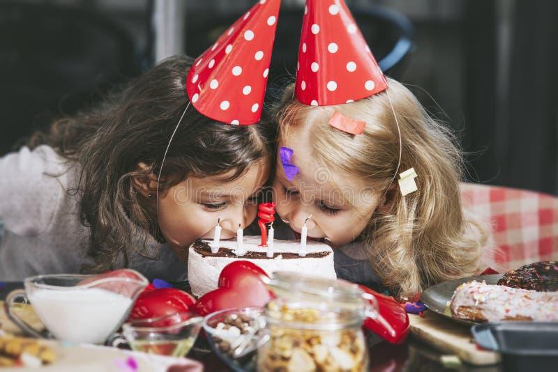 Ребенок 2 счастливый маленьких девочек празднуя день рождения с тортом на стоковое изображение rf