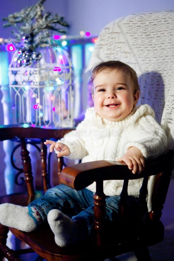 Ребенок с белым свитером сидит на стуле рядом с ветвью рождественской елки на улыбке стоковое фото