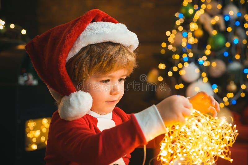 Ребенок с гарландскими огнями на рождественской ёлке и камином на канун Xmas Это чудо. Семья с детьми празднуют стоковое фото rf