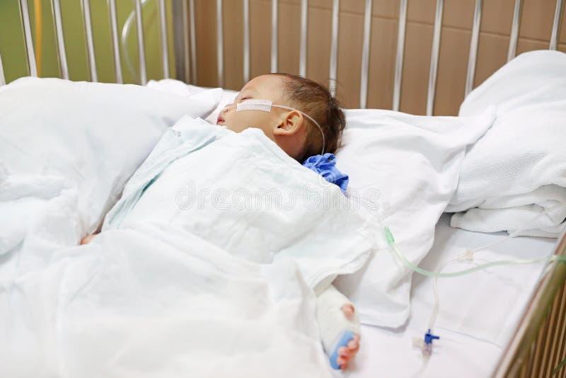 Ребенок с дыша трубкой в носе получая медицинское лечение Реанимация и прикреплять внутривенную трубку для того чтобы вручить на  стоковые изображения