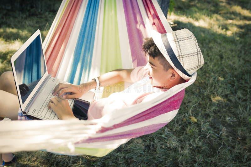Ребенок с компьтер-книжкой в гамаке стоковая фотография