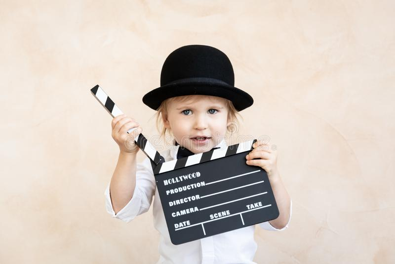 Ребенок с нумератором с хлопушкой играя дома стоковое изображение rf
