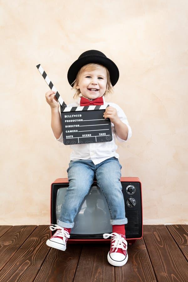 Ребенок с нумератором с хлопушкой играя дома стоковое изображение