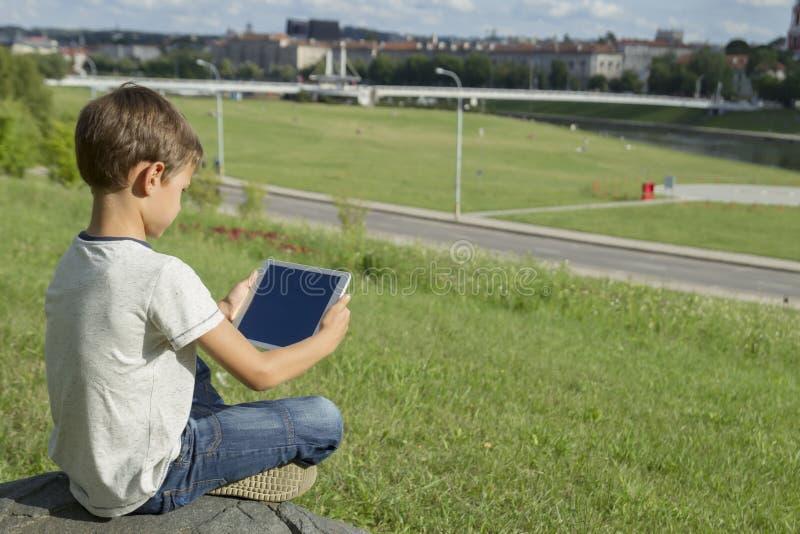 Ребенок с ПК таблетки outdoors Мальчик на траве держит компьютер задний взгляд Концепция образования людей технологии стоковые изображения