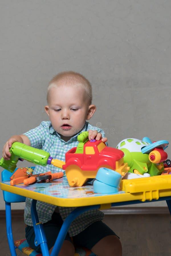 Ребенок с плоскогубцами и сверлом игрушки ремонтирует автомобили стоковая фотография rf