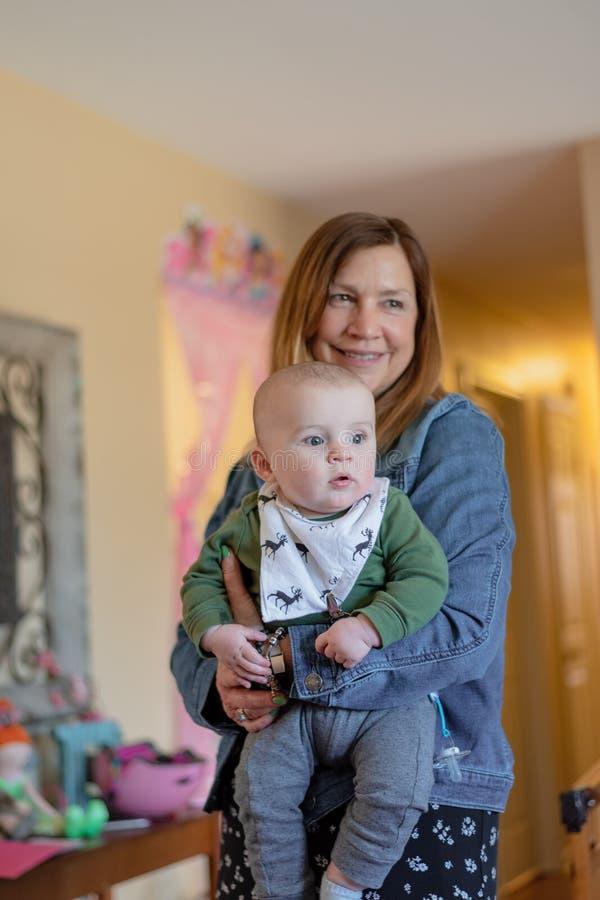 Ребенок удерживания женщины на дне рождения семьи стоковое изображение rf