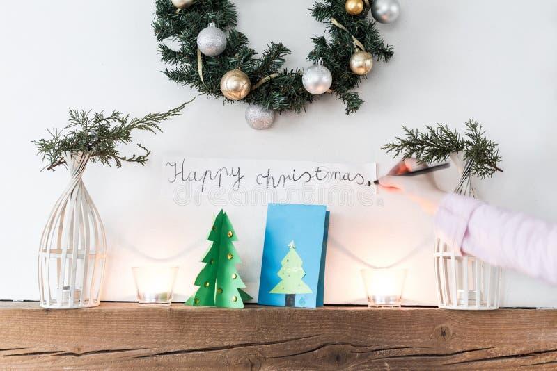 Ребенок украшая камин с знаком ` счастливого рождеств ` стоковое изображение rf