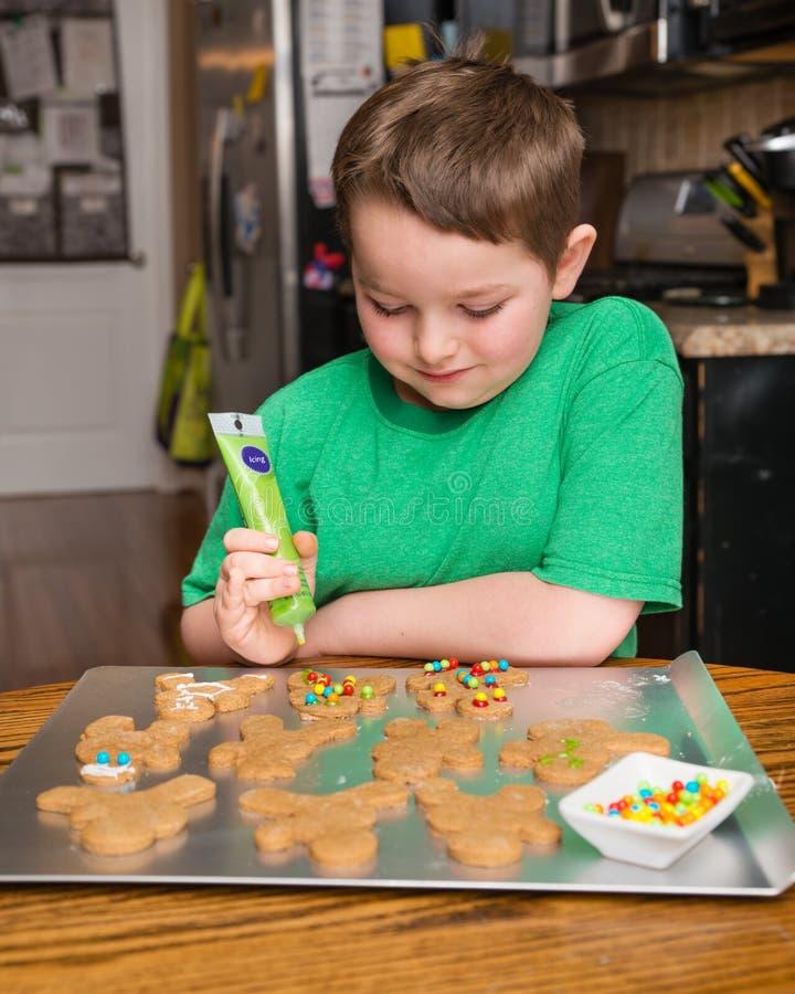 Ребенок украшая человека хлеба имбиря стоковые фото